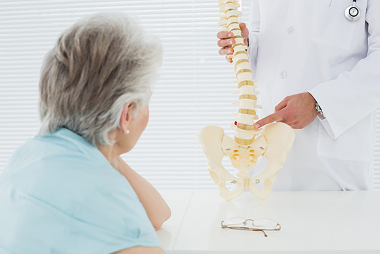 Osteopath pointing to a spinal skeleton as an elderly woman watches