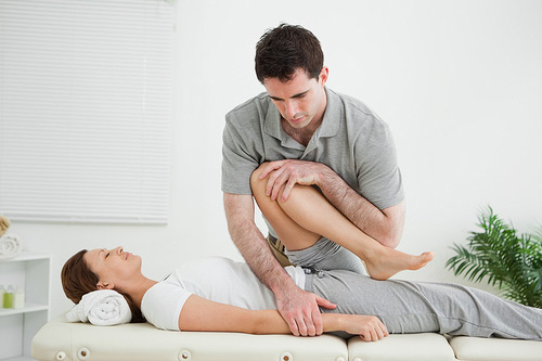 Male osteopath working on a client