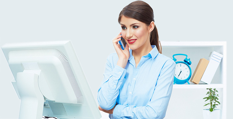 Female receptionist using a phone and computer